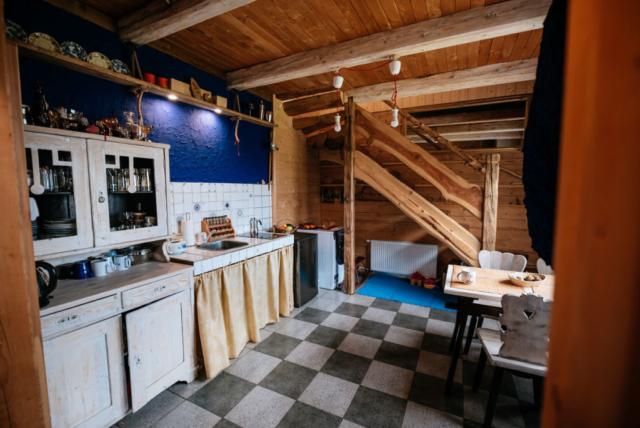 stary kredens kuchenny koło zlewu i kuchenki przy lodówce i pralce